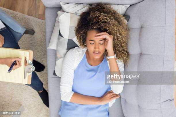 bird's eye view of therapy client laying on couch - psychiatrist's couch stock pictures, royalty-free photos & images