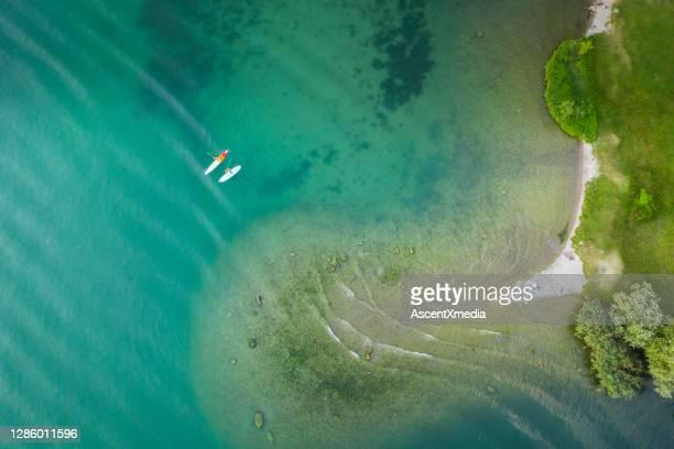 vogelperspektive von zwei paddle boardern auf einem ruhigen see bei sonnenuntergang - seeufer stock-fotos und bilder