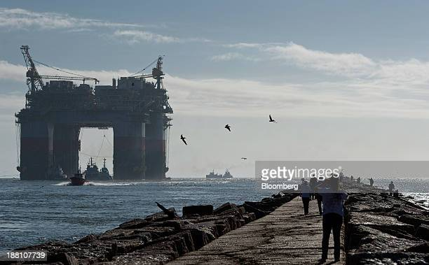 Birds fly as pedestrians watch tug boats transport the Chevron Corp Jack St Malo semisubmersible drilling and production platform to the Gulf of...