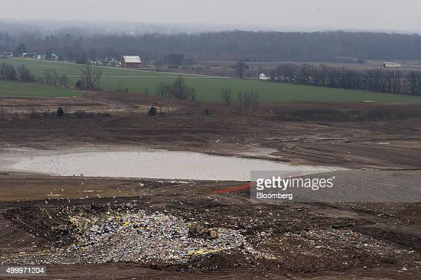 Birds fly over head as a bull dozer spreads trash to make an even layer that will be covered with fresh dirt at the Defiance County Landfill in...