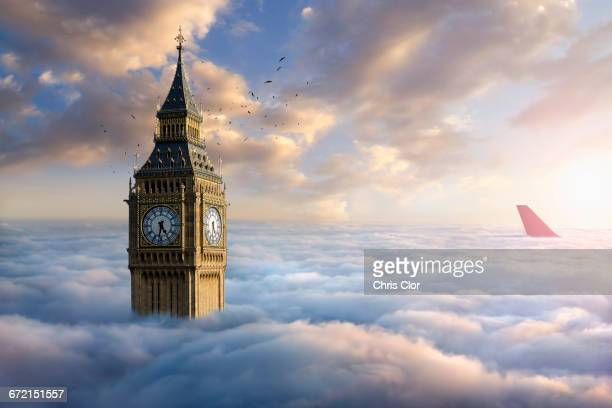 birds flying around clock tower near airplane rudder above clouds - vertical stabilizer stock pictures, royalty-free photos & images