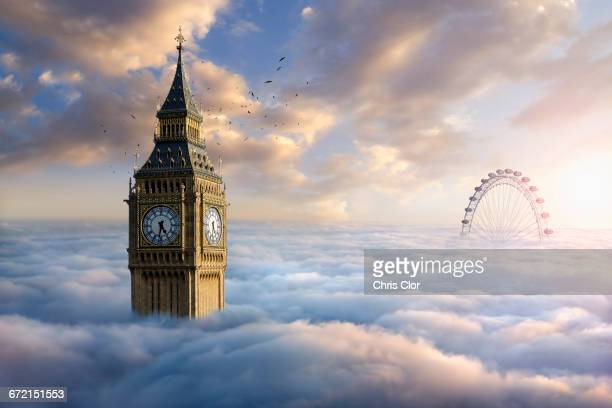 birds flying around clock tower near ferris wheel above clouds - london eye stock pictures, royalty-free photos & images
