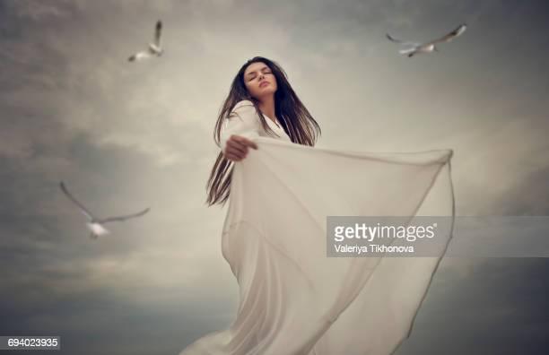 Birds flying near dancing Caucasian woman