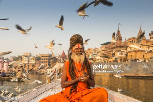 birds flying over sadhu on boat in sea against sky - religious role stock photos and pictures