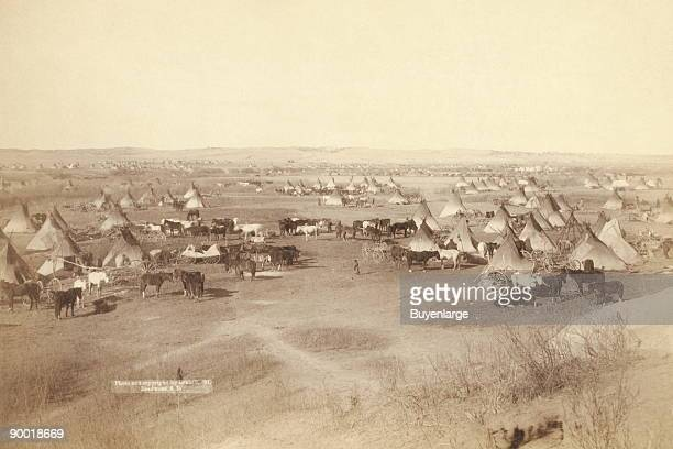 Bird'seye view of a large Lakota camp of teepees horses and wagonsprobably on or near Pine Ridge Indian Reservation