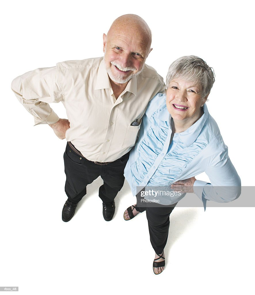 Birdseye view of an elderly couple with their hands on their hips smiling up at the camera. : Foto de stock