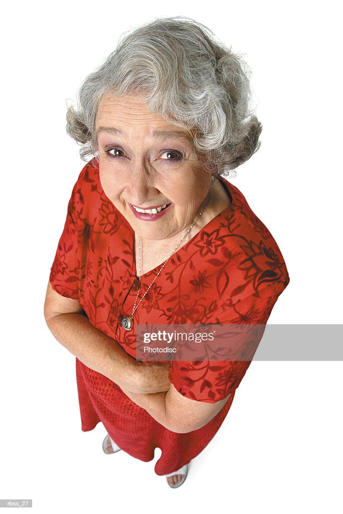 Birdseye view of an elderly woman in a red dress with her arms crossed smiling up at the camera. : Foto de stock