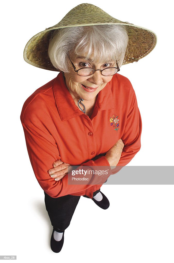 Birdseye view of an elderly woman in a red shirt and a straw hat smiling up at the camera. : Foto de stock