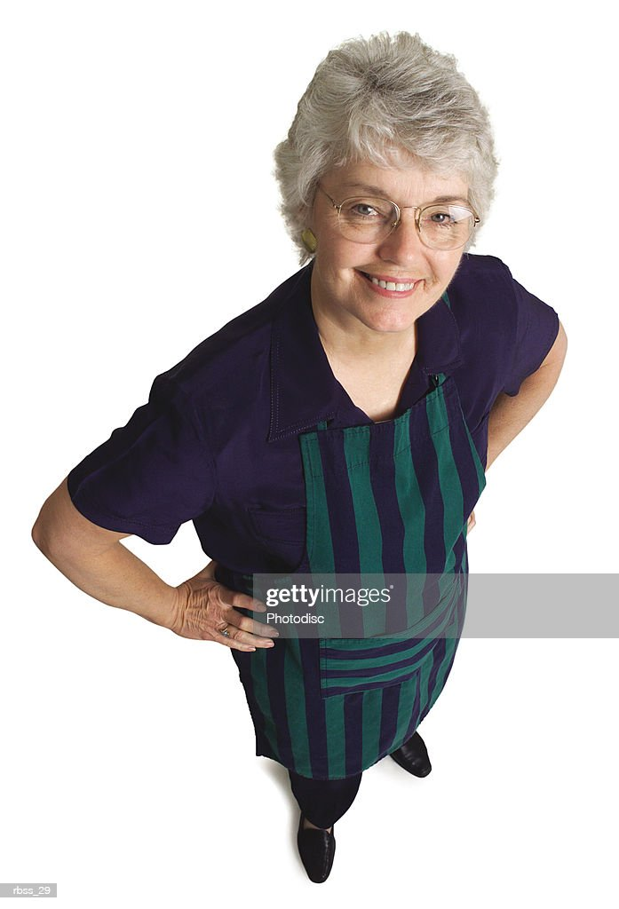 Birdseye view of an elderly woman wearing an apron smiles up at the camera. : Foto de stock
