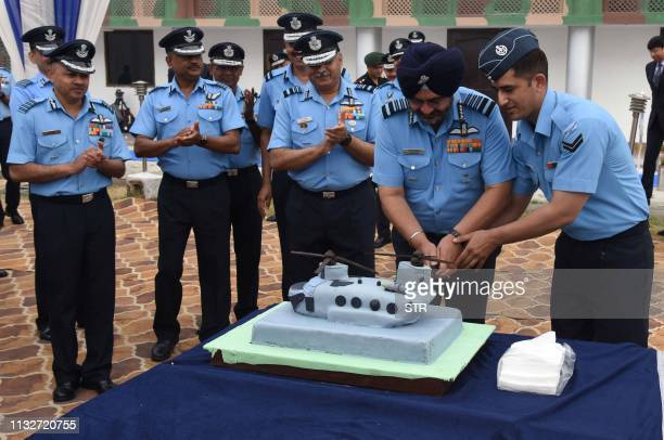 Birender Singh Dhanoa chief of the Air Staff of the Indian Air Force joins other high ranking personnel to cut a Chinook shaped cake at the induction...