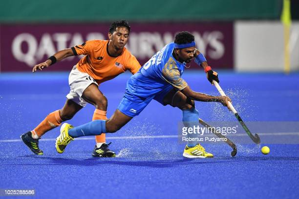 Birendra Lakra of India and Faizal Saari of Malaysia fight for the ball during Men's Hockey Semifinal match between Malaysia and India at GBK Senayan...