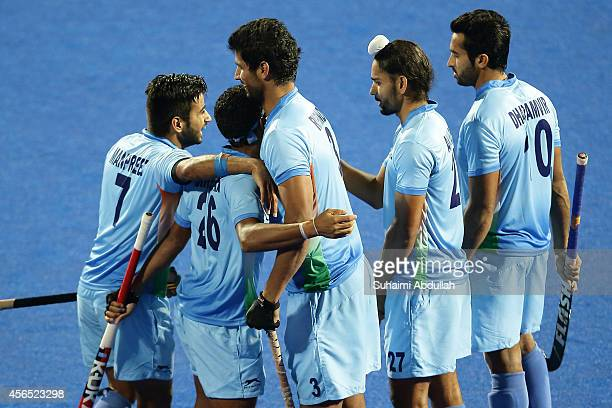 Birendra Lakra of India celebrates with teammates after scoring in the penalty shootout during the men's hockey gold medal match on day thirteen of...