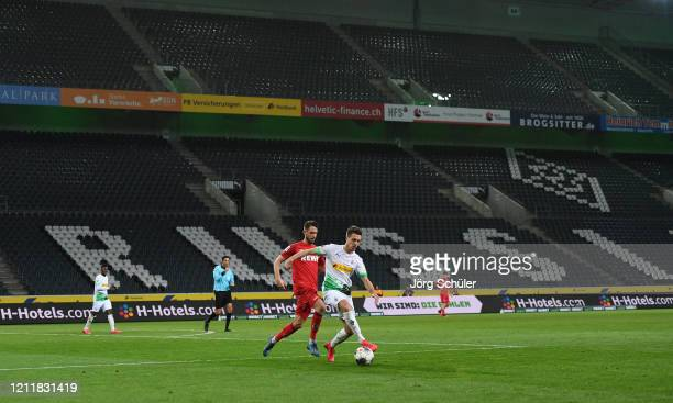 Birger Verstraete of 1. FC Koeln battles for possession with Patrick Herrmann of Borussia Monchengladbach during the Bundesliga match between...