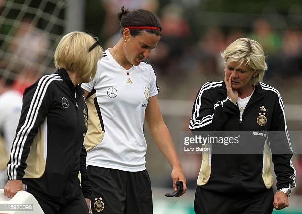 Birgit Prinz leaves injured the pitch next to head coach Silvia Neid during a German Women National Team training session on June 12 2011 in Neu...
