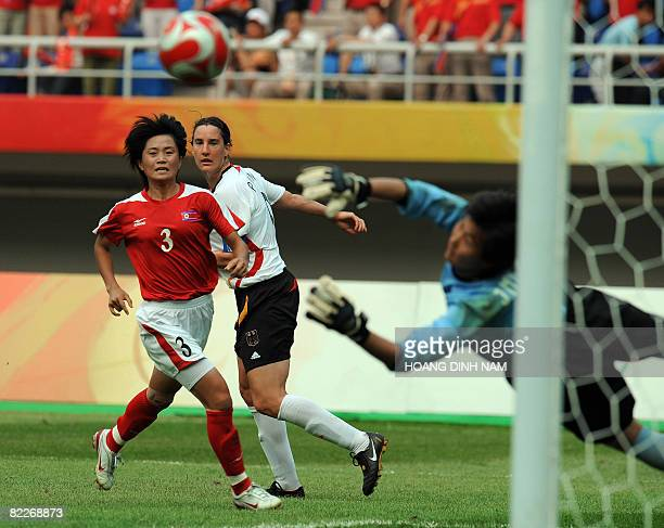 Birgit Prinz of Germany looks on after shooting as goalkeeper Jon Myong Hui of North Korea dives for a block in their women's first round group F...