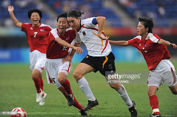 Birgit Prinz of Germany vies for the ball with North korea's Kong HyeOk and Sonu KyongSun to set up the winning goal in their women's first round...