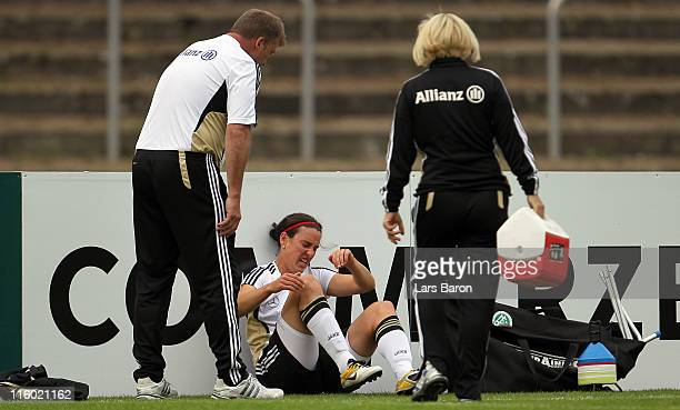 Birgit Prinz sits injured next to the pitch during a German Women National Team training session on June 12 2011 in Neu Isenburg Germany