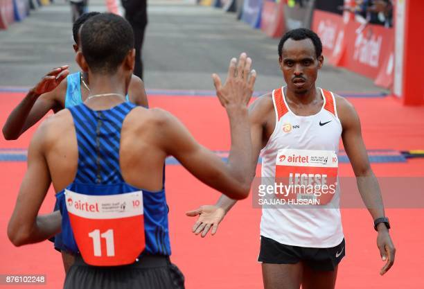 Birhanu Legese of Ethiopia celebrates with Andamlak Belihu of Ethiopia after he crosses the finish line to win the Delhi Half Marathon in New Delhi...