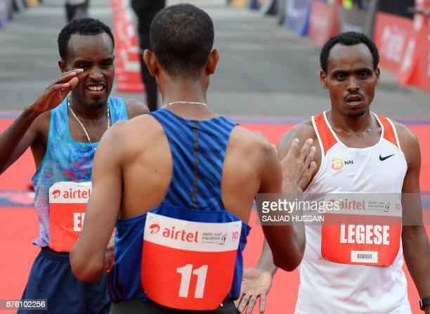 Birhanu Legese of Ethiopia celebrates with Andamlak Belihu of Ethiopia and Leonard Korir of US after he crosses the finish line to win the Delhi Half...