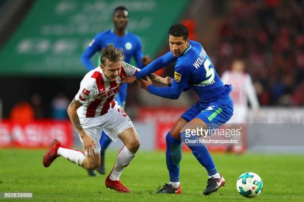 Birk Risa of FC Koeln battles for the ball with Jeffrey Bruma of Wolfsburg during the Bundesliga match between 1 FC Koeln and VfL Wolfsburg at...