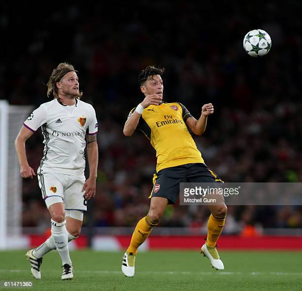 Birkir Bjarnason of Basel and Mesut Ozil of Arsenal during the Champions League match between Arsenal and FC Basel at The Emirates Stadium on...