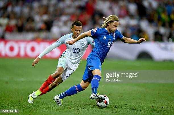 Birkir Bjarnason of Iceland and Dele Alli of England compete for the ball during the UEFA EURO 2016 round of 16 match between England and Iceland at...