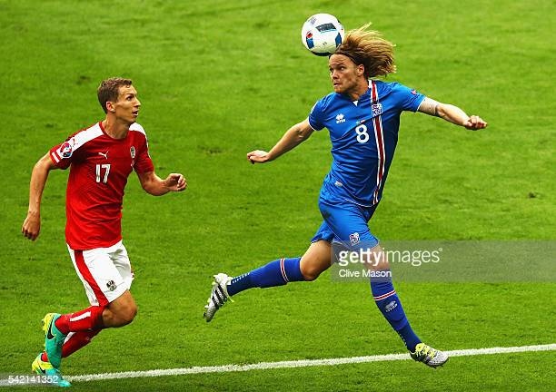 Birkir Bjarnason of Iceland clears under pressure from Florian Klein of Austria during the UEFA EURO 2016 Group F match between Iceland and Austria...