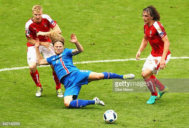 Birkir Bjarnason of Iceland goes down under the challenge of Marc Janko of Austria and Julian Baumgartlinger of Austria during the UEFA EURO 2016...