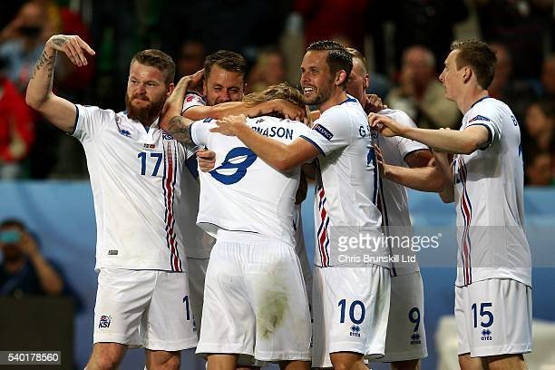 Birkir Bjarnason of Iceland is congratulated by his teammates after scoring the equaliser during the UEFA Euro 2016 Group F match between Portugal...