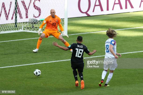 Birkir Bjarnason of Iceland shoots under pressure from Eduardo Salvio of Argentina during the 2018 FIFA World Cup Russia group D match between...
