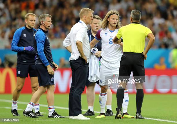 Birkir Bjarnason of Iceland speaks with fourth official John Pitti as he prepares to come back on after recieving medical treatment during the 2018...