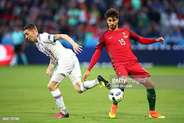 Birkir Saevarsson of Iceland and Andre Gomes of Portugal compete for the ball during the UEFA EURO 2016 Group F match between Portugal and Iceland at...