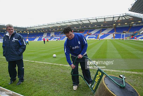 Birmingham City Manager Steve Bruce watches as a groundsman trys to clear the waterlogged pitch before the FA Barclaycard Premiership match between...