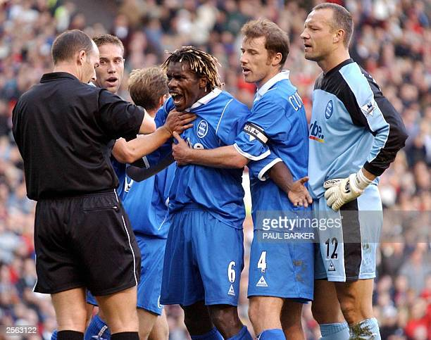 Birmingham City's Aliou Cisse is restrained by team mates while arguing with the referee after goalkeeper Maik Taylor had brought down Manchester...