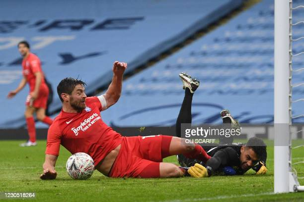 Birmingham City's English striker Lukas Jutkiewicz slides in to challenge Manchester City's US goalkeeper Zack Steffen during the English FA Cup...