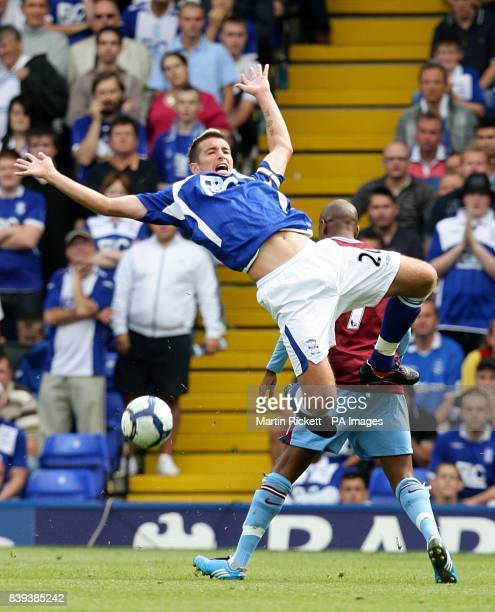Birmingham City's Franck Queudrue flies through the air after a challenge by Aston Villa's Ashley Young
