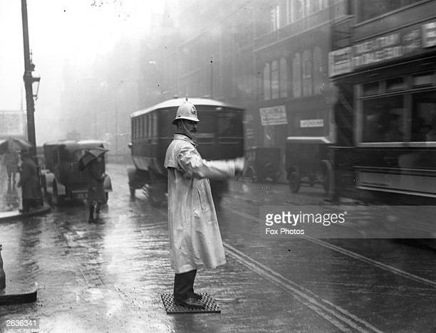 A Birmingham policeman stands on a rubber mat while directing traffic in the rain