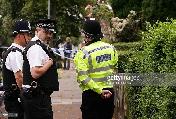 Birmingham, UNITED KINGDOM: Police stand guard at a house on Bankdale Rd in Birmingham after three men were arrested there in connection with the 21...