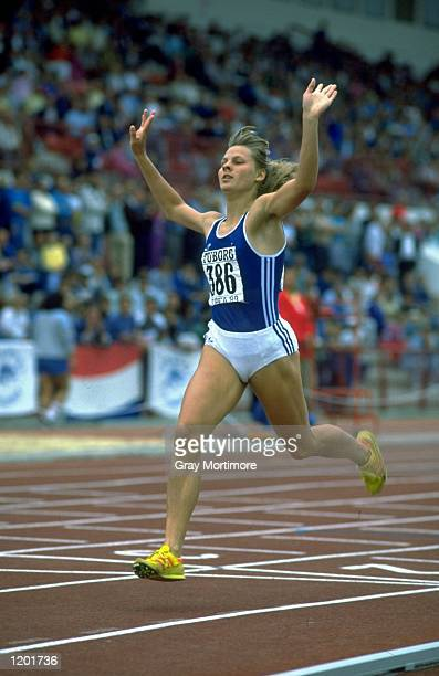 Birta Bruhns of East Germany raises her arms aloft as she crosses the line to win the 800 metres event during the European Junior Championships in...