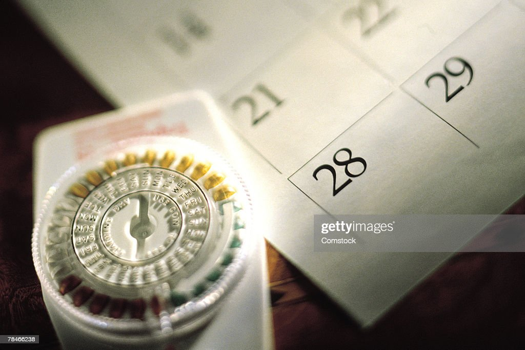 Birth control pills and calendar : Stock Photo