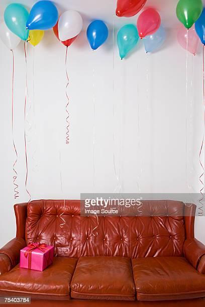 Birthday balloons and gift on sofa