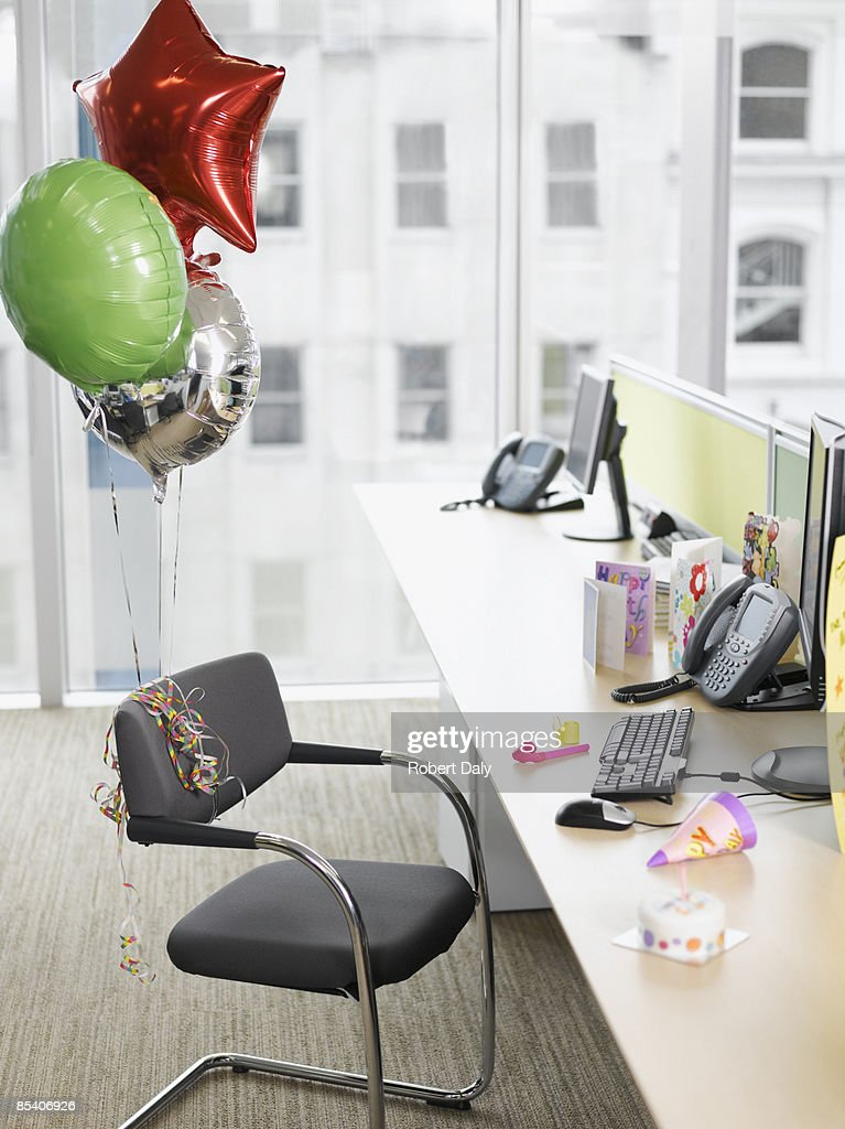 Birthday balloons tied to office chair : Stock Photo