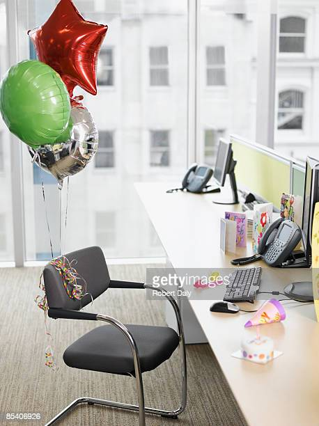 birthday balloons tied to office chair - birthday balloons stock photos and pictures