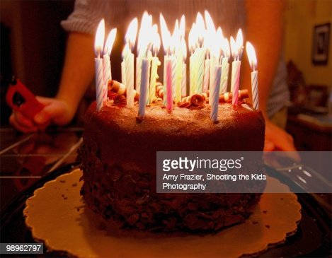 A Birthday Cake Ablaze With Many Candles Stock Photo