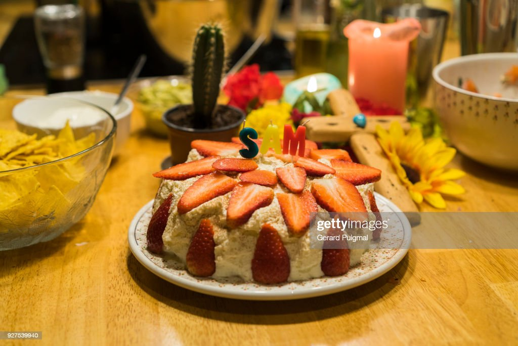 A Birthday Cake On Table Surrounded By Snacks Stock Photo