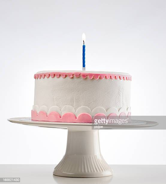 birthday cake on cakestand with one burning candle - birthday cake stock photos and pictures