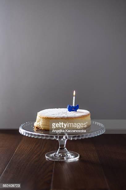 Birthday cake on cakestand with one burning candle