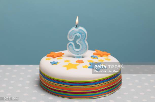 birthday cake with a number 3 candle burning on top. - number 3 stock pictures, royalty-free photos & images