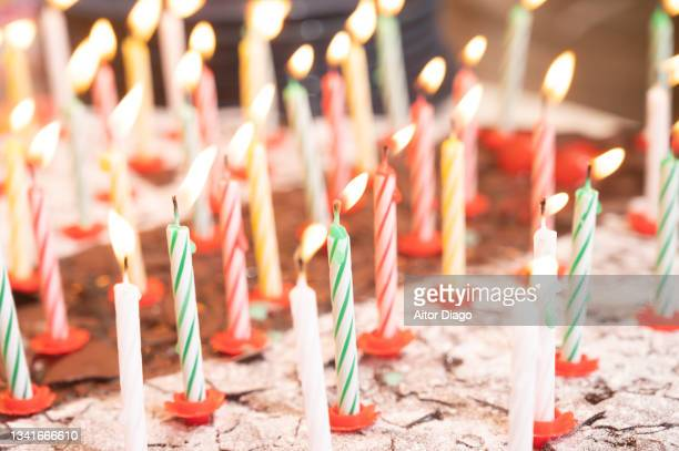 a birthday cake with lighted candles blowing with the wind. - 100th anniversary stock pictures, royalty-free photos & images