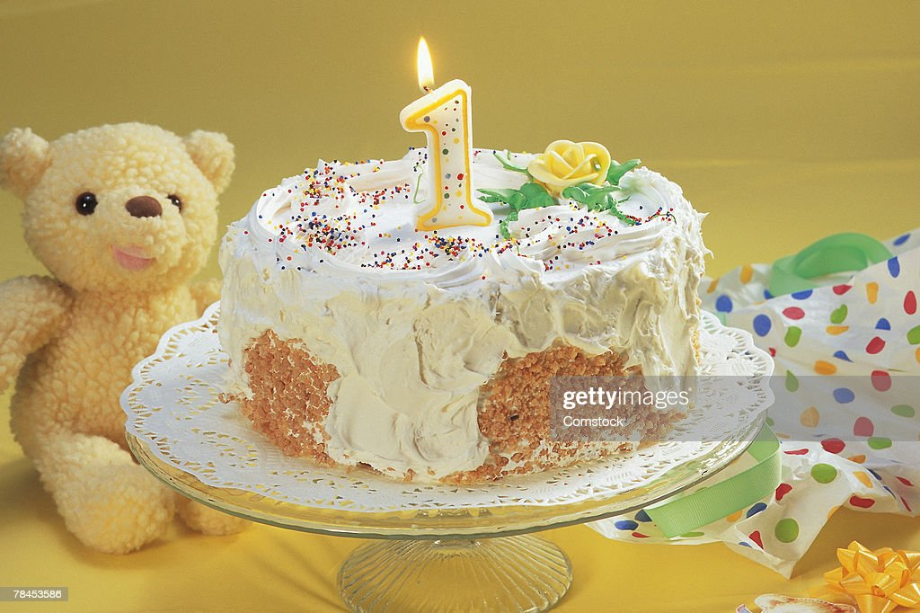 Birthday cake with one candle and teddy bear : Stockfoto